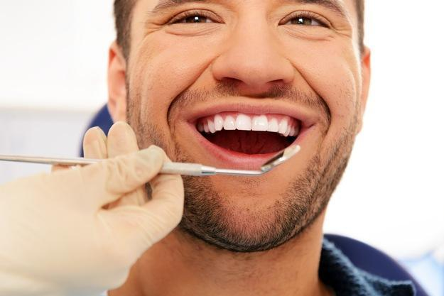 man smiling in dental exam chair I sedation dentistry glenmont ny