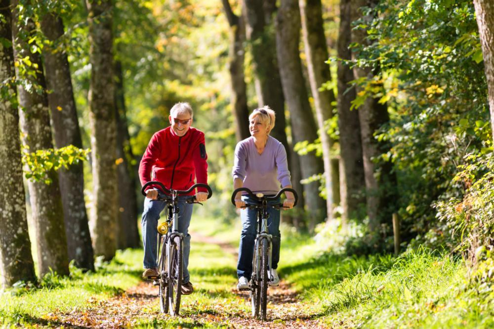 Image of couple riding their bikes in the forest | Bethlehem Town Family Dental | Glenmont, NY